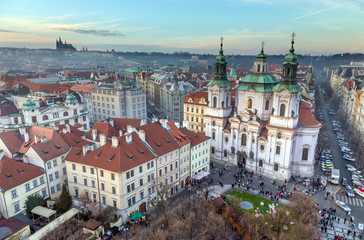 Panoramic view of Prague at sunset, St. Nicholas Church on the foreground, Czech Republic.