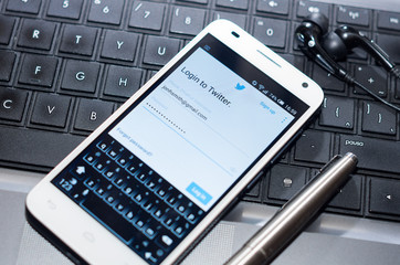 QUITO, ECUADOR - AUGUST 3, 2015: White smartphone closeup lying next to silver pen on laptop keyboard with Twitter website screen visible