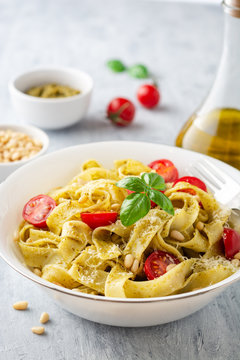 Fettuccine pasta with sauce pesto, cherry tomatoes, pine nuts and parmesan cheese on concrete background. Selective focus.