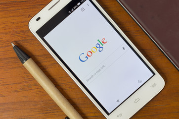 QUITO, ECUADOR - AUGUST 3, 2015: White smartphone lying on wooden desk with screen activated displaying Google search site next to a pen, business and communication concept
