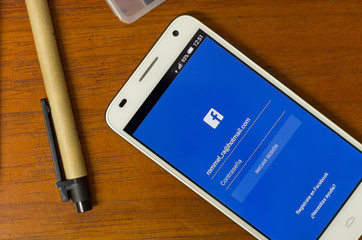 QUITO, ECUADOR - AUGUST 3, 2015: White smartphone lying on desk with Facebook screen open next to a pen, business and communication concept
