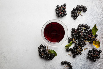 homemade black chokeberry wine or liqueur with ripe berries, top view Fototapete