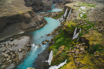 Scenic landscape view of incredible Sigoldugljufur canyon in highlands with turquoise river, Iceland. Volcanic landscape on background. Popular tourist attraction.
