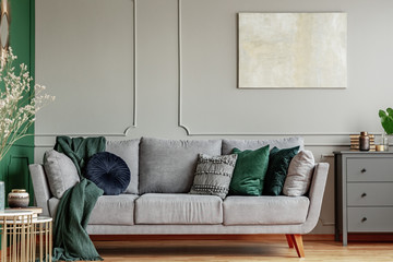 Pillows on long comfortable living room couch in grey scandinavian style interior with wooden floor Wall mural
