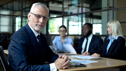 Elderly company director looking camera, office colleagues discussing strategy