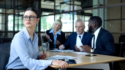 Sad female manager looking window during office meeting, workload tiredness