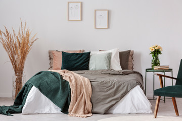Colorful pillows in king size bed with duvet and blankets in hygge inspired bedroom
