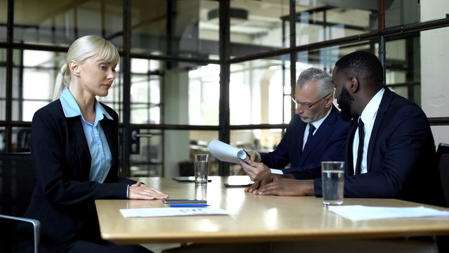 Male colleagues ignoring female partner discussing business issues, woman rights