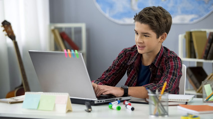 Schoolboy playing online game on laptop at home sitting table, teenage free time