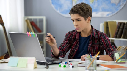 Male child doing homework in room using e-book on laptop, contemporary education