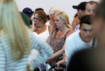 Tourists react as they queue up in a check-in service at Cancun International Airport after Thomas Cook, the world's oldest travel firm collapsed