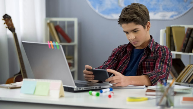 Lazy kid enthusiastically playing smartphone game instead homework, discipline