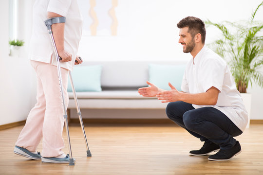 Senior woman at hospital learning how to walk on crunches and supporting male nurse