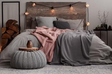 Yerba matte on wooden plate on grey woolen pouf in stylish bedroom interior
