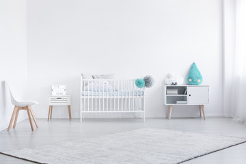 Blue cushion on cabinet next to cradle in white baby's bedroom interior with chair and carpet. Real photo