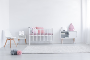 Pink pillow on cabinet and white chair in simple kid's room interior with carpet and cradle. Real photo