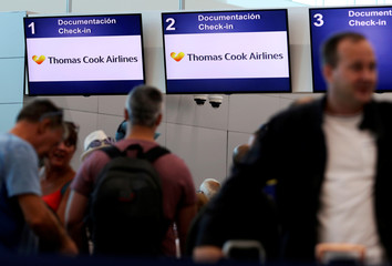 Tourists queue up in a check-in service at Cancun International Airport after Thomas Cook, the world's oldest travel firm collapsed