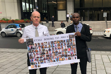 Men who lost family in the Ethiopian Airlines crash hold a sign outside a Federal Aviation Administration briefing in Montreal