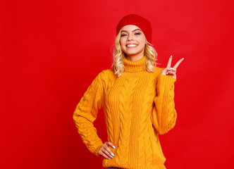 happy emotional cheerful girl laughing  with knitted autumn cap  on colored red background.