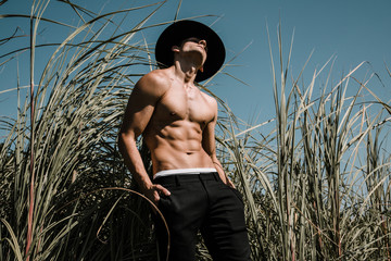 Portrait of a handsome shirtless young man in a black hat. Fashion country concept. Outdoor shot.