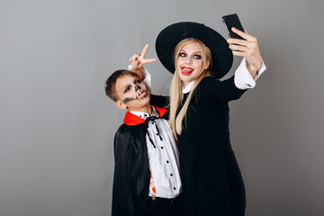 Mother and son in  fancy dress showing victory gesture and making selfie against studio background