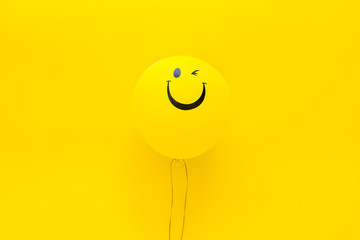 Happiness emotion. Yellow balloon with smile on yellow background top view copy space