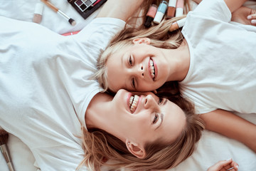I love my mom. Happy Mothers Day. Top view of beautiful mom with her little cute daughter are having fun at home. Doing makeup and smiling while lying on bed.
