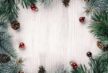 Fototapete - Creative frame made of Christmas fir branches on white wooden background with red decoration, pine cones. Xmas and New Year theme. Flat lay, top view
