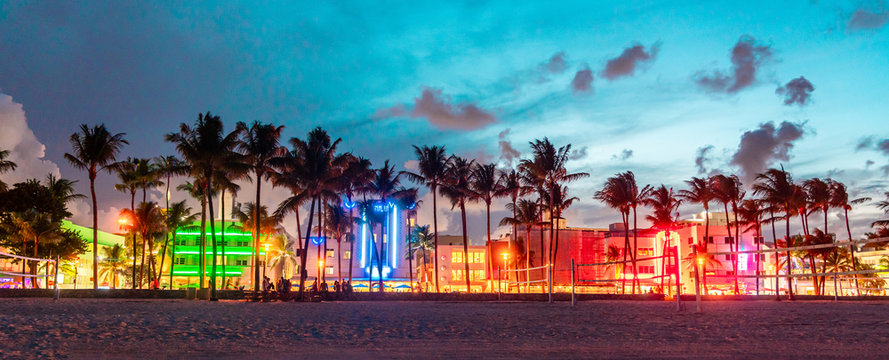 Miami Beach Ocean Drive panorama with hotels and restaurants at sunset. City skyline with palm trees at night. Art deco nightlife on South beach