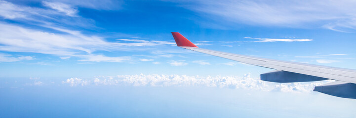 Panorama of plane wing above nice blue sky