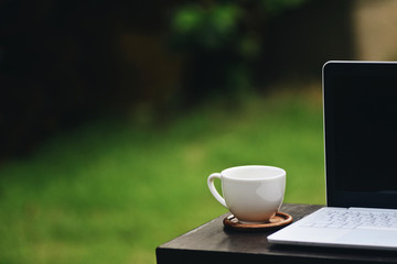 Businesses happen everywhere, just have inspiration. The picture of white laptop, a coffee cup above wooden table on blurred green grass background with copyspace. Selective focus