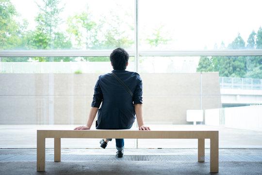 大きな窓の前に設置されたベンチに座る男性