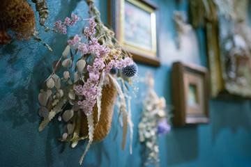 青い壁にかけられたドライフラワーのスワッグと額縁