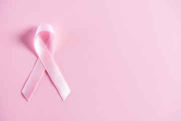Pink ribbon on pink pastel paper background for supporting breast cancer awareness month campaign.