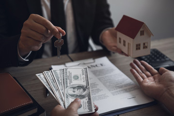 Businessman handed the house model and new homeowner giving money to real estate trading.