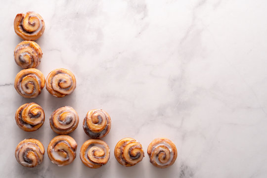 Homemade baked cinnamon rolls with marble slab background and space for text.