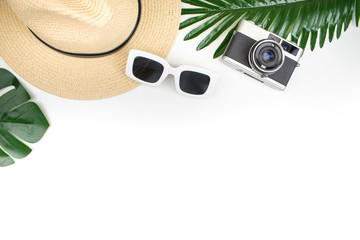 Top view, tourist equipment with straw hats, film cameras, sunglasses and summer foliage on a white background. Summer item. Travel concept.