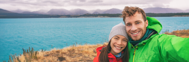 Wall Mural - Happy tourists couple taking selfie at Pukaki blue lake, New Zealand autumn travel outdoor lifestyle banner panorama.