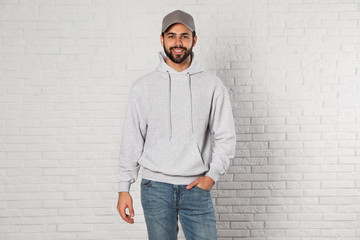 Wall Mural - Portrait of young man in sweater at brick wall. Mock up for design