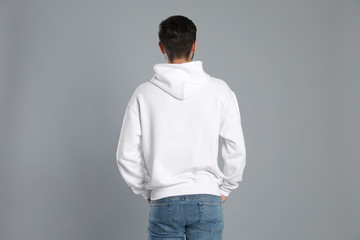 Wall Mural - Young man in sweater on grey background. Mock up for design