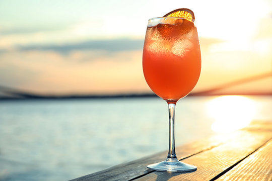 Glass of fresh summer cocktail on wooden table outdoors at sunset. Space for text
