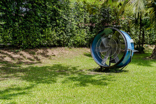 Big electric fan blows into the air to cool down the area outside on a hot summer day, big ventilators in park.