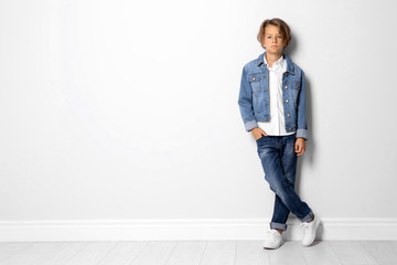 Cute little boy in casual outfit near white wall. Space for text