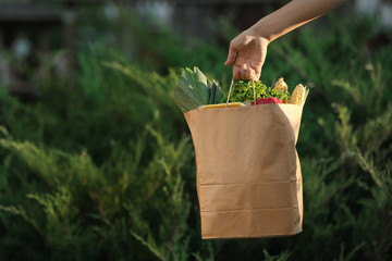 Woman holding paper bag with fresh vegetables outdoors, space for text Wall mural