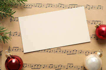 Fotobehang - Flat lay composition with Christmas decorations and blank card on music sheets, space for text