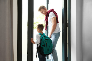 Happy father and little child with school bag in doorway
