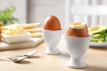 Cups with soft boiled eggs on wooden table, space for text. Healthy breakfast