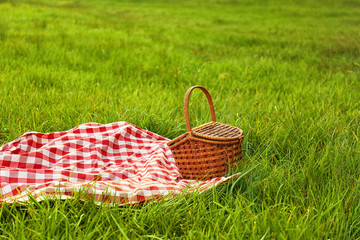 Fotobehang Picnic blanket and basket on grass in park