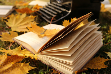 Writing Concept.Autumn Books. retro black typewriter and books with yellow maple leaves on the lawn. books about autumn