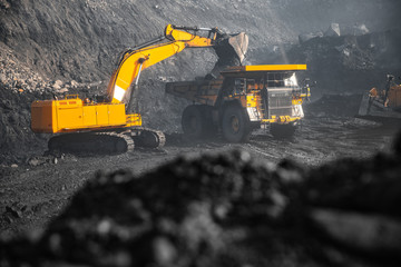 Open pit mine industry, excavator loading coal on big yellow mining truck for anthracite